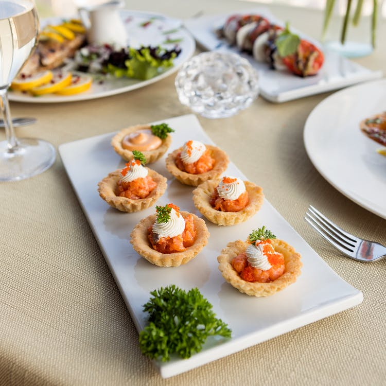 a tray of prosciutto and goat cheese tarts