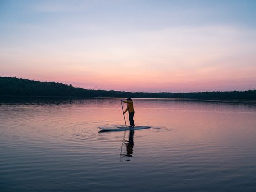 A lone man riding a board in the middle of a lake