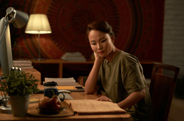 Image of a woman reading on a table with coffee and a lamp.